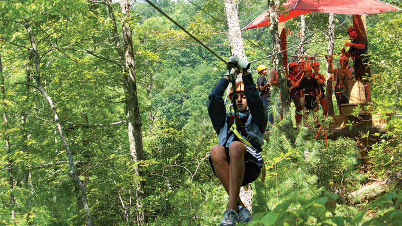 Girl riding a zip line through the trees
